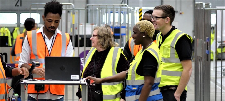 2 Frauen und ein Mann, alle in gelben Sicherheitswesten, stehen an einem Laptop-Tisch. Ein Amazon Mitarbeiter erklärt ihnen etwas auf dem Bildschirm.