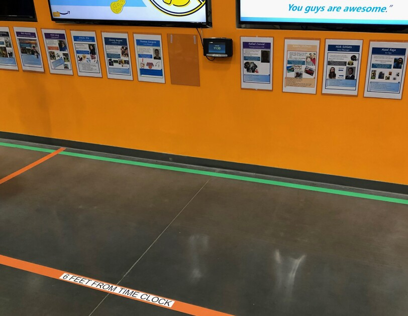 Taped lines on the floor at an Amazon fulfillment center, to encourage social distancing among associates.