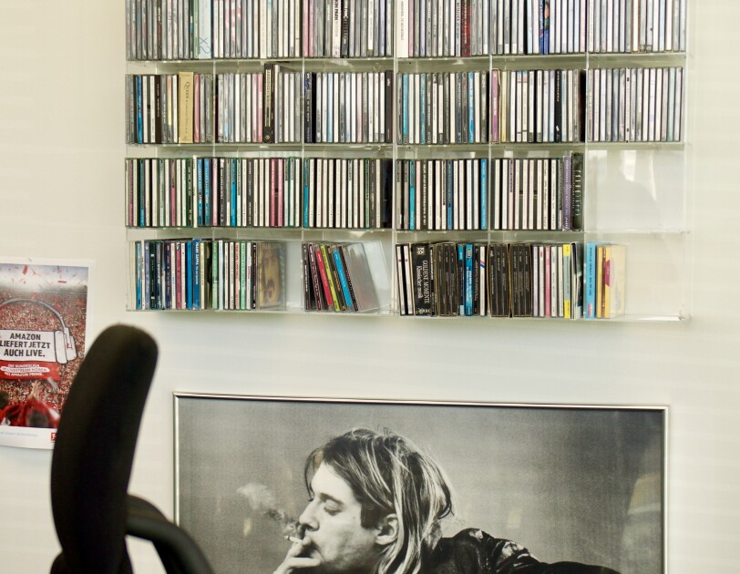 Eine Bürowand zeigt von unten nach oben: ein handsigniertes Porträt von Kurt Cubain, ein gefülltes CD-Regal und rechts: einen roten Fußball-Fanschal, der an der Wand befestigt wurde.