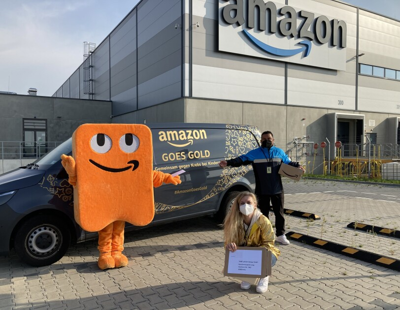 """Amazon Maskottchen Peccy, eine Mitarbeiterin und ein Lieferpartner stehen vor einem mit """"Amazon Goes Gold"""" beschrifteten Liefervan. Im Hintergrund ist ein Amazon Verteilzentrum zu sehen."""