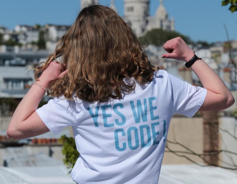 """Une jeune fille montre son t-shirt sur lequel """"Yes We Code"""" est inscrit"""