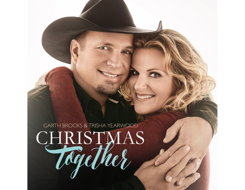 Garth Brooks and Trisha Yearwood face the camera, smiling, as they share an embrace. Garth wears a black cowboy hat and button down. Trisha wears her hair in loose curls and a burgundy long-sleeve top.