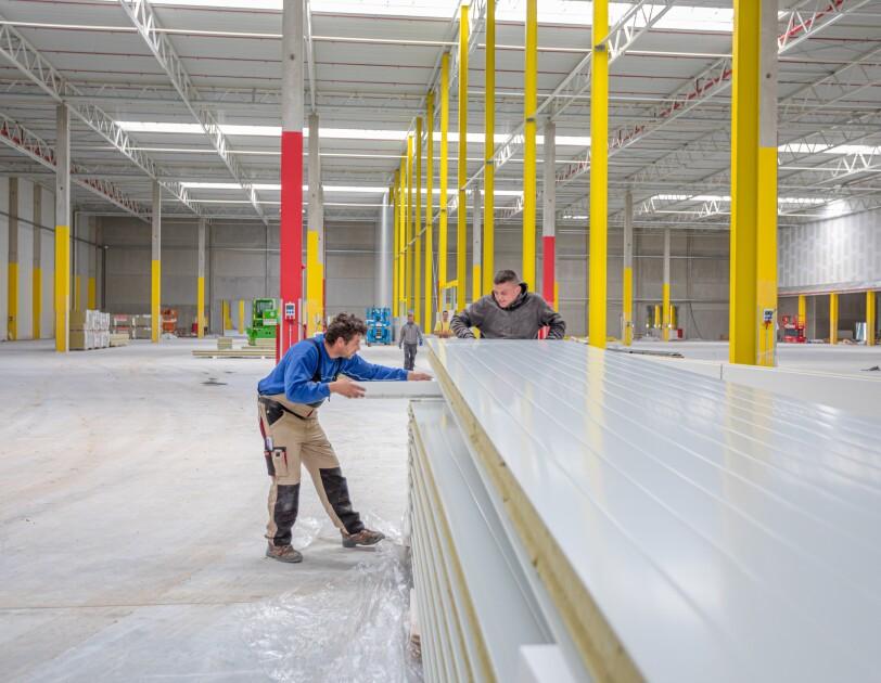 Eine leere Halle: im Vordergrund sind 2 Bauerbeiter beschäftigt, lange Dielen zu stapeln.