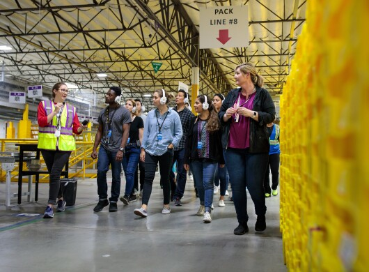 A tour guide leads a group of people wearing headphones on a tour of an Amazon Fulfillment center