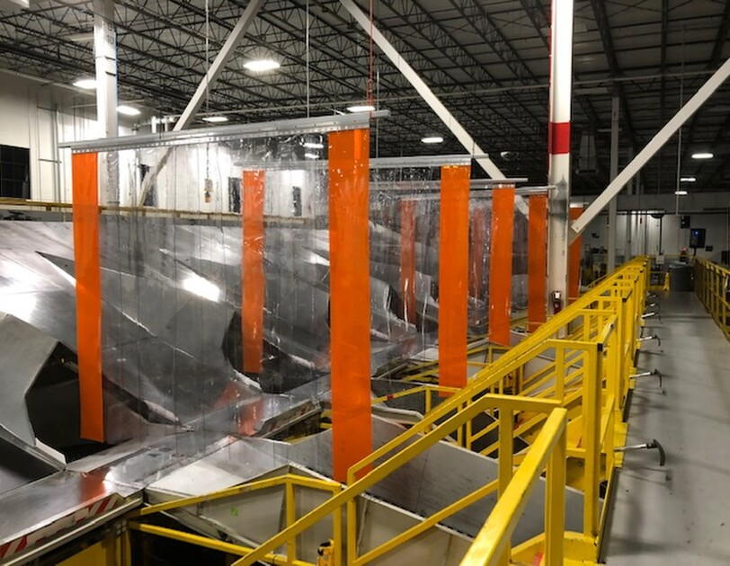 View inside an Amazon fulfillment center showing physical barriers between chutes to encourage social distancing.