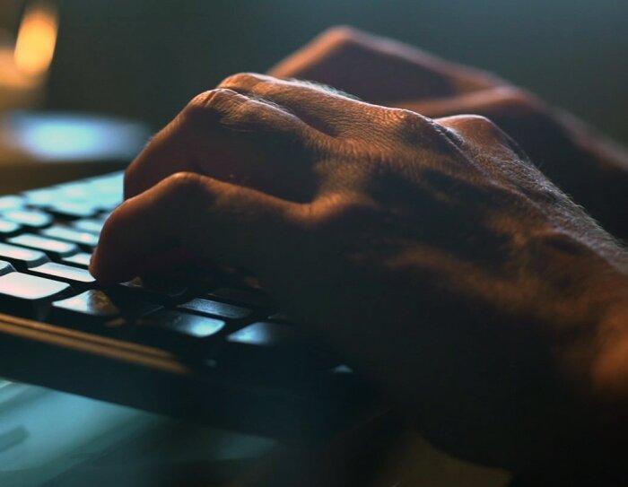 Primer plano de dos manos y un teclado.