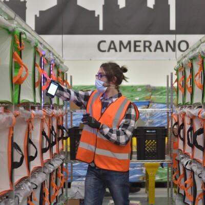 Un corridoio di pacchi in un magazzino Amazon. Al centro un dipendente smista i pacchi, sullo sfondo si legge la scritta Camerano