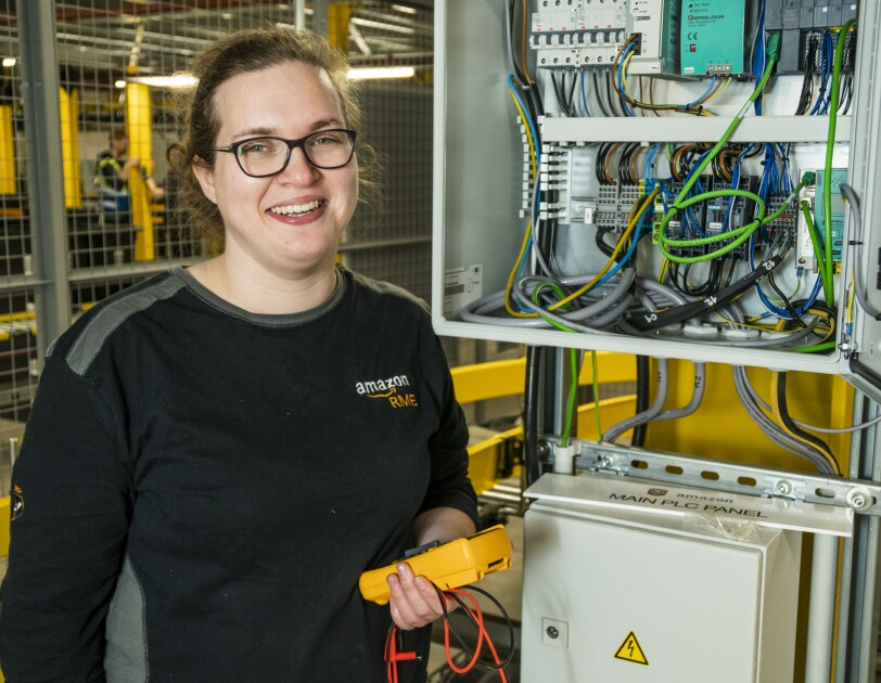 Nicola Elliott, automation engineering apprentice standing in front of an electrical unit.