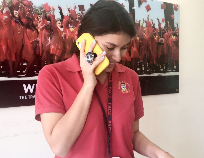 A teenage girl talks on a smartphone. She wears a red polo shirt with a school logo and stands in front of a poster of graduating students.