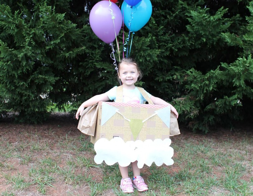 A young girl in a hot air balloon Halloween costume. She wears a box with pennants at the top, and paper clouds at the bottom. Above her float several colorful balloons.