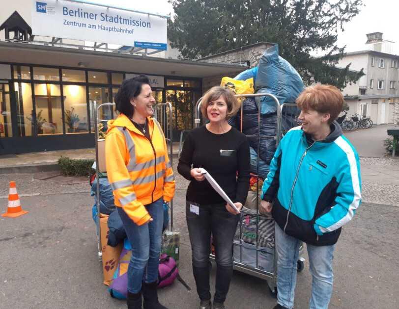 Drei Frauen haben sich vor dem Gebäude der Berliner Bahnhofsmission vor 2 Hubwagen aufgestellt. Auf den Wagen sind diverse Pakete.