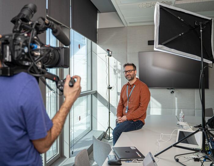 Daniel Méndez, Content Program Manager de Alexa, en una sala de trabajo de las oficinas de Amazon en un momento de la grabación. Daniel aparece en el fondo con una camisa de color marrón. Las ventanas están en el lado izquierdo. En primer plano y desenfocado aparece el cámara con una camiseta azul de manga corta.