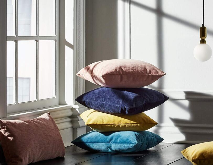 A stack of four pillows sit on a wood floor. Pillows are (from bottom) peacock blue, ocre, indigo and dusty pink. They sit in front of a low, paneled window, and besides another pink pillow on the left, and an ocre one on the right.