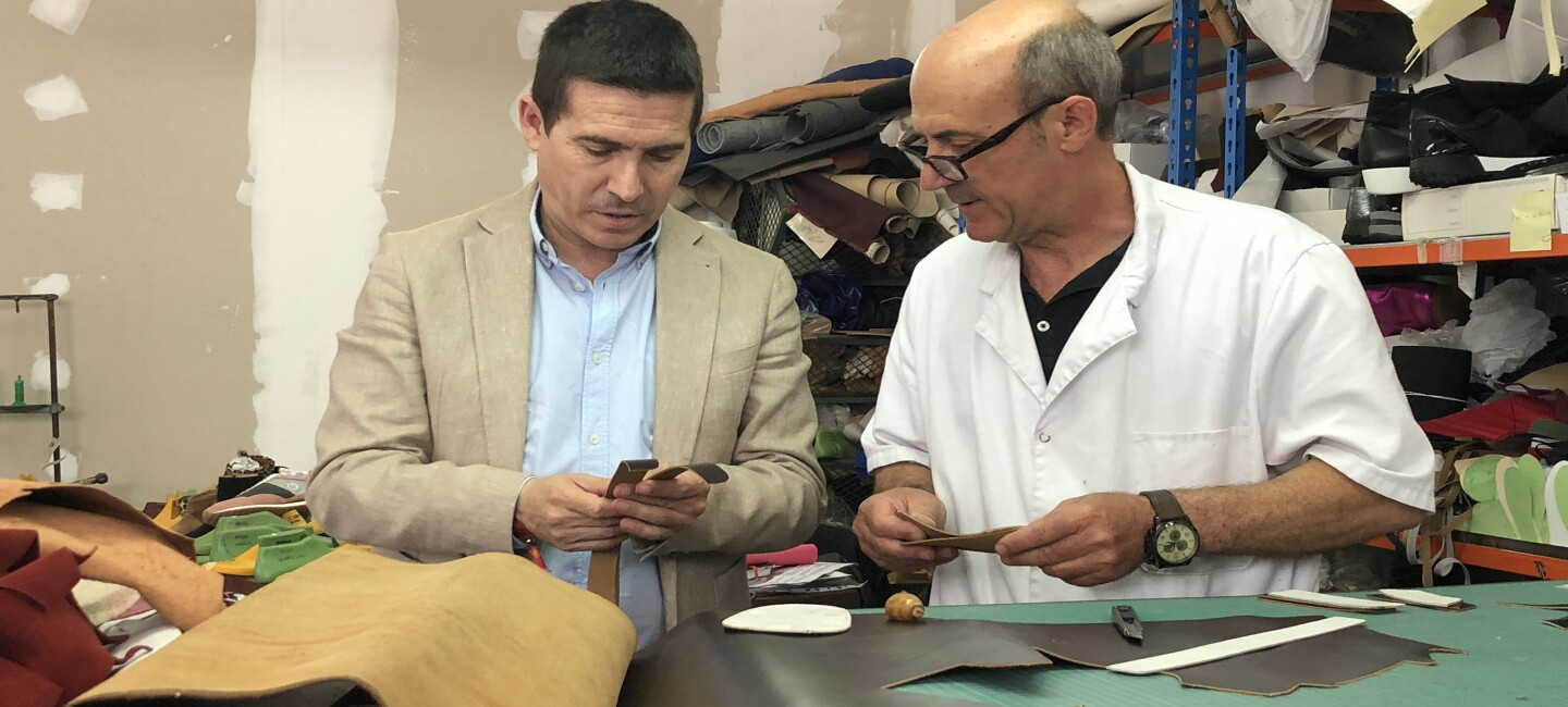 José Antonio Mollá, founder of Castellanisimos,  a Spanish shoemaker is working on leather choices with his employee in a room of leather samples for shoes.