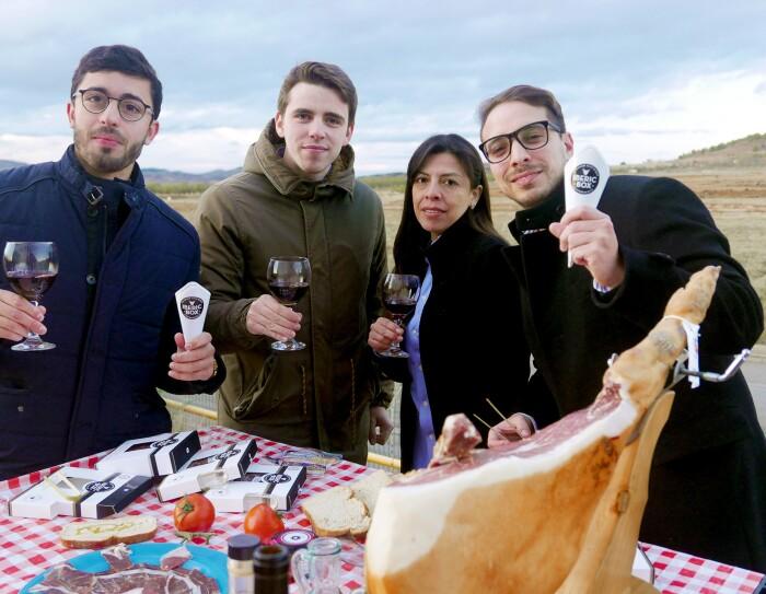 El equipo de Iberic Box, 4 jóvenes que no superan los 40 años, están posando detrás de un mesa lleva de comida y brindan con copas de vino tinto. En la izquierda, el CEO de la startup, David González, con una copa de vino tinto y un sobre de jamón, acompañado de tres colegas del equipo. Todos visten con chaquetas de invierno. La mesa tiene un mantel de cuadros, un jamón con el jamonero, un plato de jamón, las cajas de Iberic Box, una botella de aceite y otra de vino. El fondo de la foto es el cielo azul.