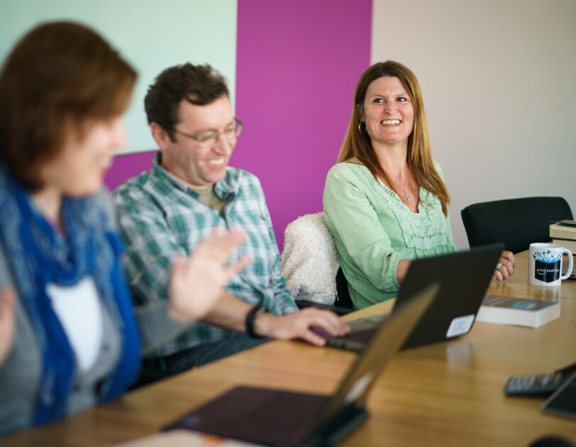 Three members of the Amazon Books editorial team. On the right, a woman gestures. The man to her right laughs, and a woman on the right smiles. They sit at a conference table behind laptop computers.