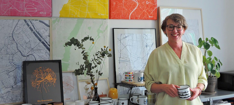 Eine Frau mit kurzen blonen Haaren und einer gelben Bluse steht vor einer Wand mit Bildern. Auf den Bildern sind die Karten verschiedener Städte zu sehen.