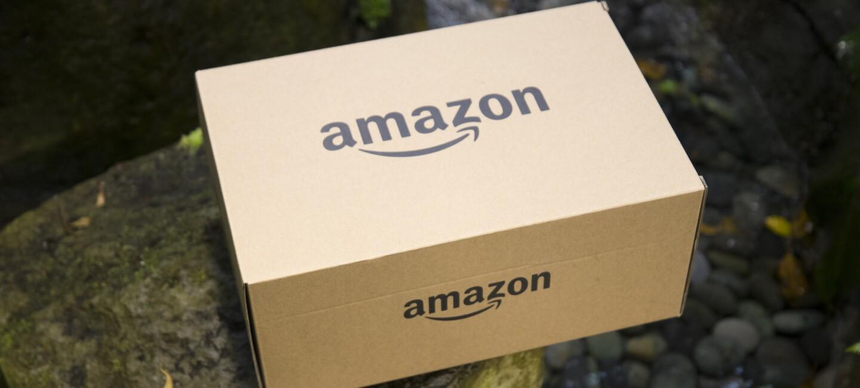 Un pacco con il logo di Amazon poggiato su una pietra. Sullo sfondo, a destra, si intravede un piccolo corso d'acqua.