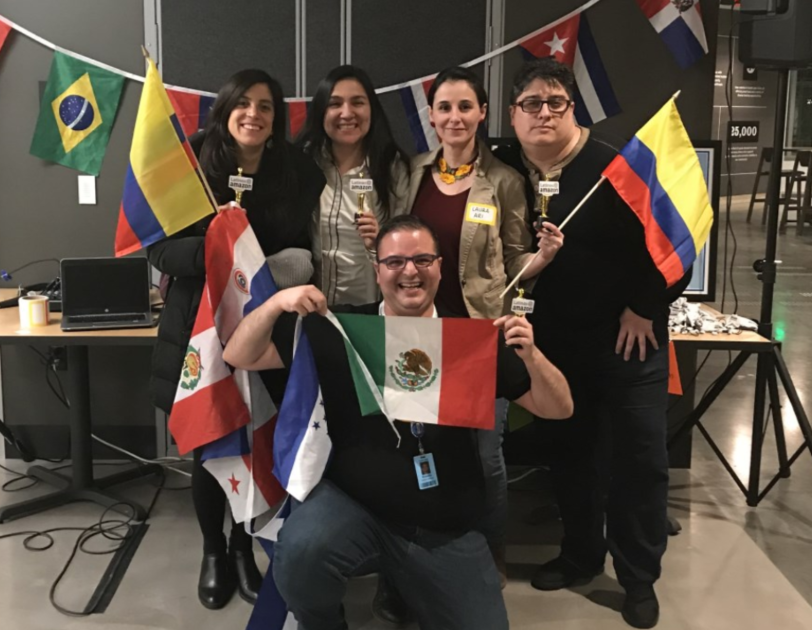 A photo of Amazon employees posing with various flags at the 2019 Hispanic Heritage Month celebration.