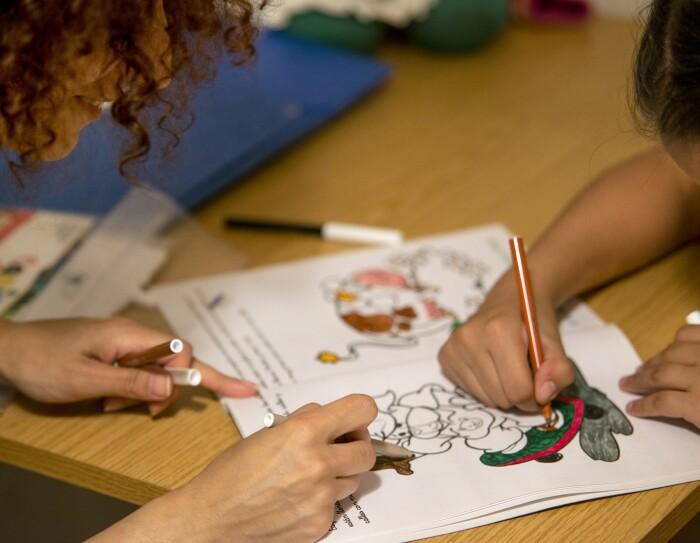 En el primer plano hay una mesa las manos de una  niña a la derecha coloreando un cuento con un rotulador marrón. A la izquierda las manos y la cabeza se una madre con el pelo rizado ayudando a pintar a su hija. La mesa es dec color marrón y titne más coloes y una carpeta de color azul.