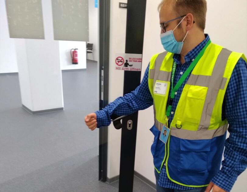 Mitarbeiter in Sicherheitsweste und Mundschutz öffnet die Türe mit der Armbeuge.