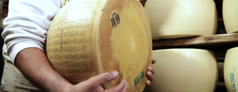 Primo piano di una forma di Parmiggiano Reggiano retta dalle mani di un uomo di cui non si vede il volto. Sullo sfondo, due scaffali con alcuni formaggi non stagionati.