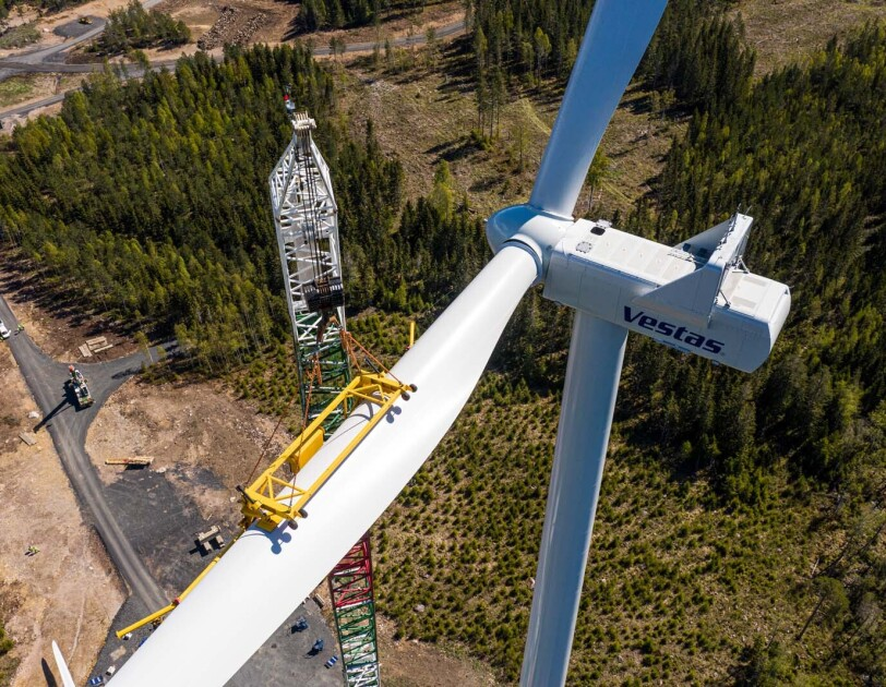 Birds-eye view looking down on a crane assembling a wind turbine.
