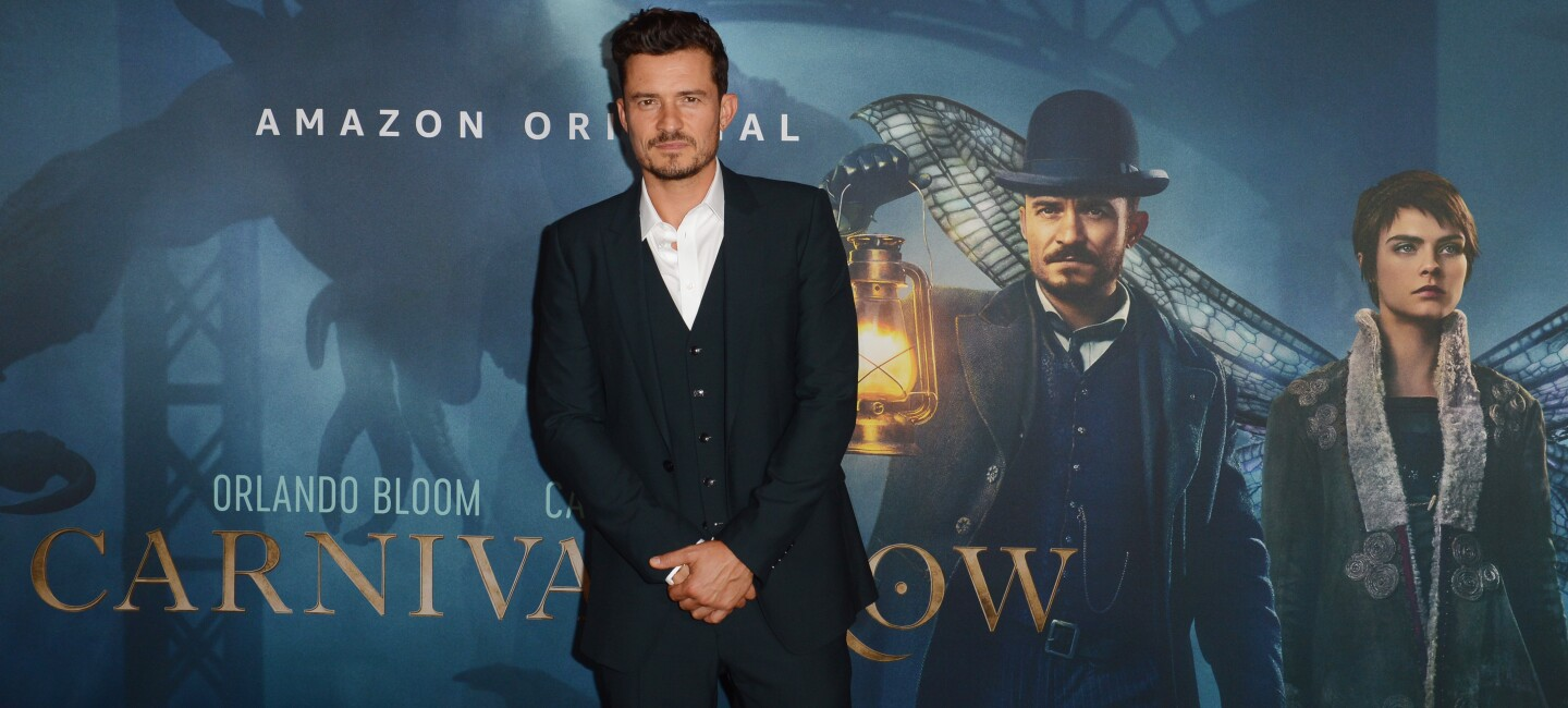 "Orlando Bloom bei der Amazon Prime Premiere ""Carnival Row"" in der Astor Film Lounge vor einem Filmplakat."