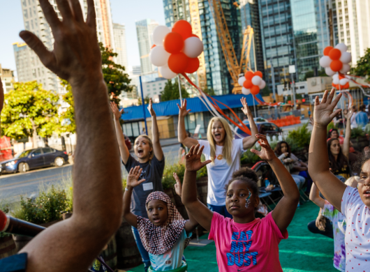 In an Amazon community event, a man leads a group of kids in a performance in front of Mary's Place.