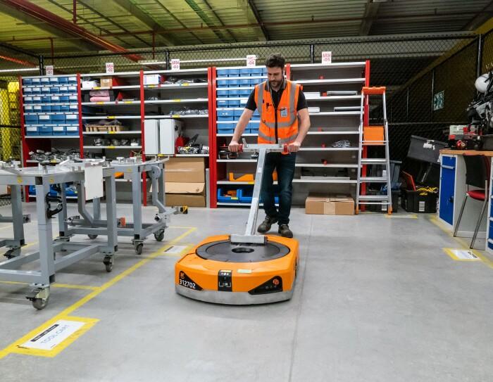Raúl Cruz, técnico senior de mantenimiento en robótica, manipulando un robot (drive). Vestido con el chaleco naranja, Raúl aparece trasladando un robot con una herramienta específica que sujeta el drive por su parte inferior. De fondo de foto aparecen estanterías propias del lugar de reparación de los robots.