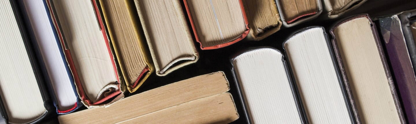 Many hardbound books stacked tightly together at various angles, seen edge on.