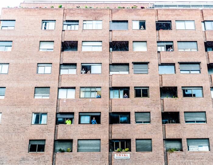 #SeriesDesdeMiBalcón visitó la plaza Felipe II en el distrito de Salamanca el jueves 16 de abril. En la foto aparece un edificio de color marrón con gente en las terrazas y en las ventanas.