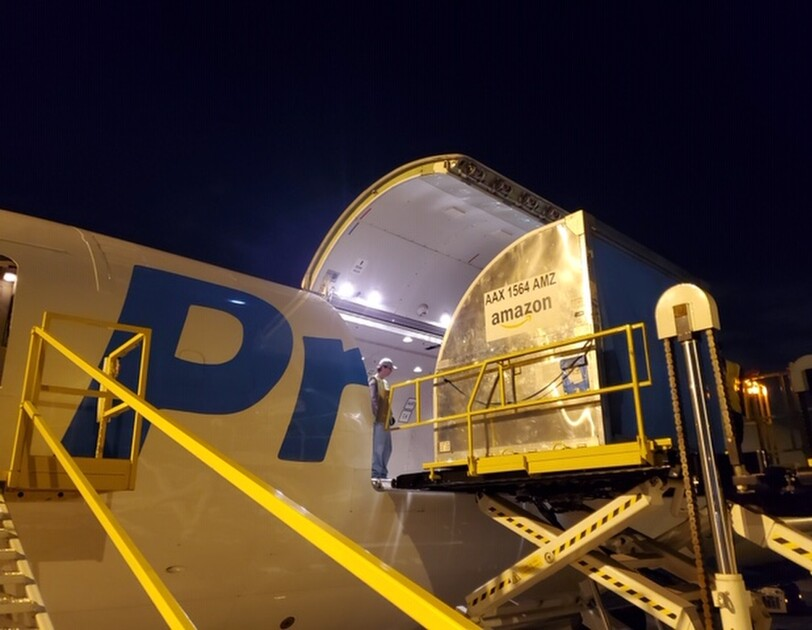 Nighttime image of airport ground equipment lifting cargo onto an Amazon Air cargo plane.