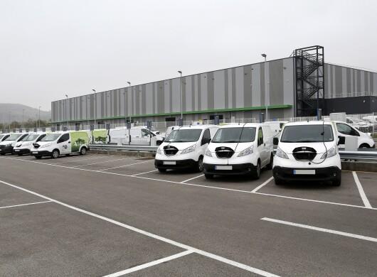 En el centro logístico de Vicálvaro en Madrid aparecen 7 furgonetas eléctricas cargando batería. De fondo el centro logístico de color gris. Las furgonetas son blancas y tienenla parte trasera de color verde. Están en el aparcamiento de delante del centro logístico.