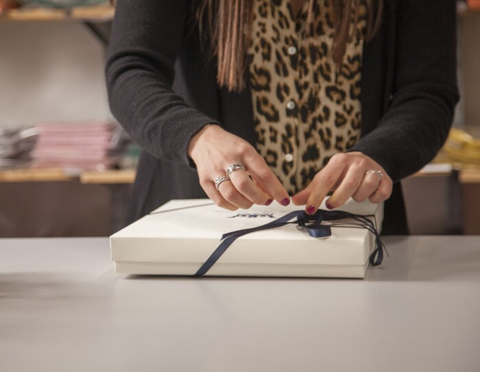 Le mani di un'impiegata Dalle Piane confezionano un ordine per un cliente con una scatola e un nastro.