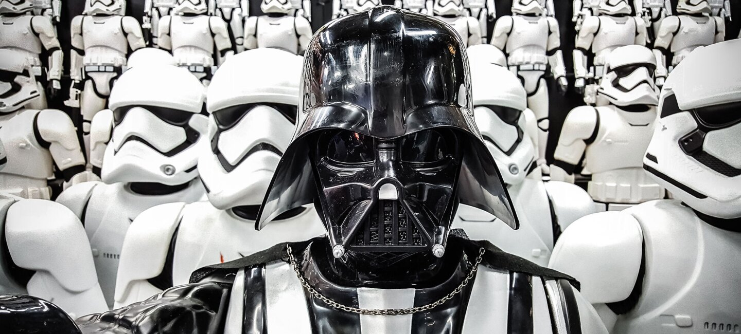 Darth Vader, front and center, staring into the camera, with row after row of Stormtroopers behind him