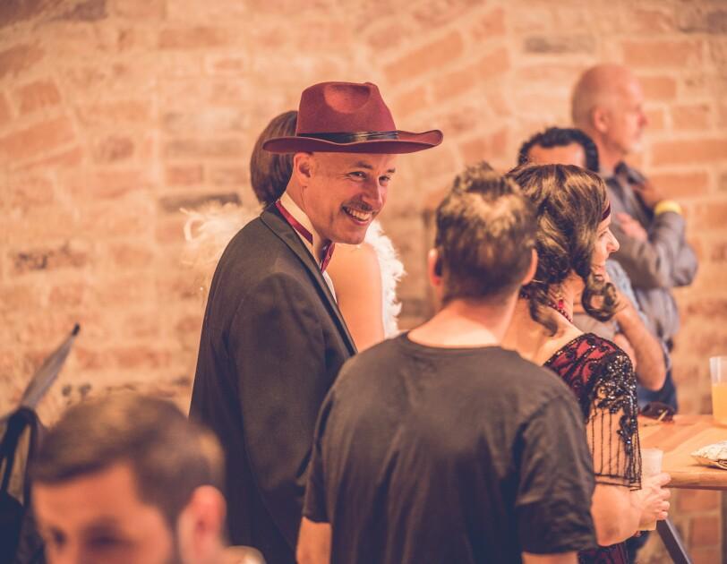 Ein Mann mit Zwanziger-Jahre Hut und Anzug spricht mit einer Frau, die von hinten zu sehen ist
