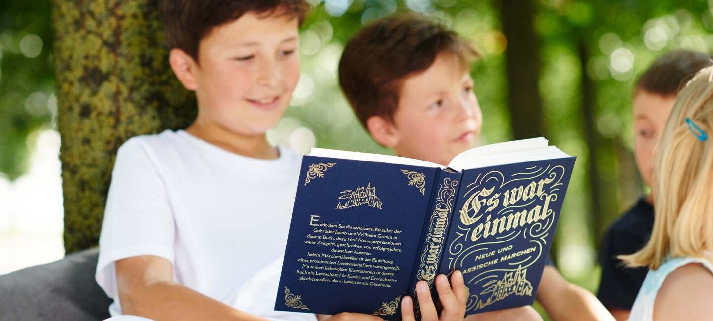 """Kind liest aus Märchenbuch """"Es war einmal"""""""