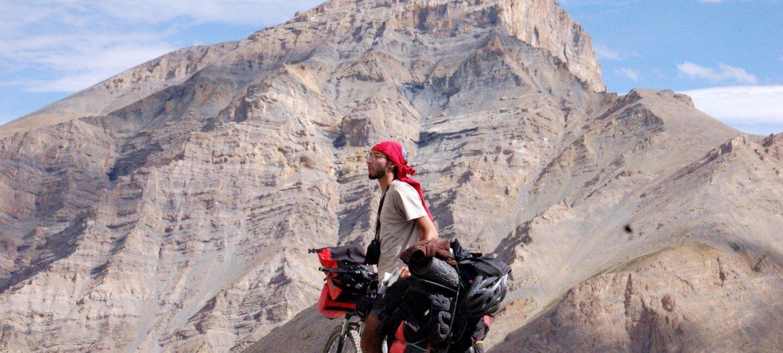 Karim Fahssis se tient à côté de son vélo chargé de sacs de voyage au milieu d'un paysage désertique. Il porte un foulard sur la tête. Derrière lui une montagne aride.