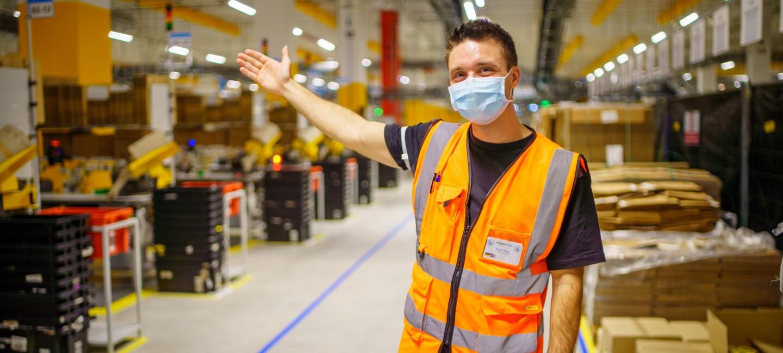 Bastian Dressel mit einem Willkommensgruß im Logistikzentrum.