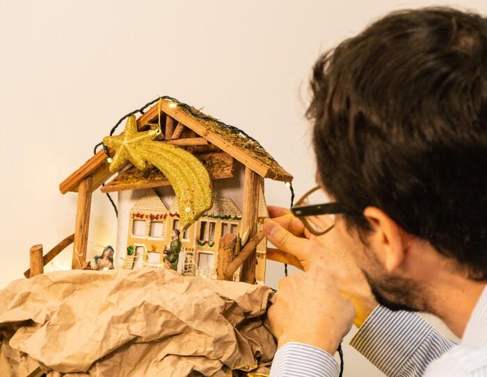 Fernando Poucell es arquitecto y empezó a trabajar en Amazon hace tres meses. En la foto se ve Fernando de perfil colocando un portal de Belén hecho a mano con maderas, luces y cartones. Él tiene el pelo negro corto, lleva barba y una gafas.
