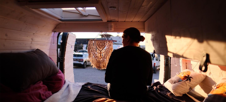 Ein Mann mit Zopf sitzt in seinem Camper Van. Er sitzt mit dem Rücken zur Kamera und wir von der Sonne angeleuchtet.