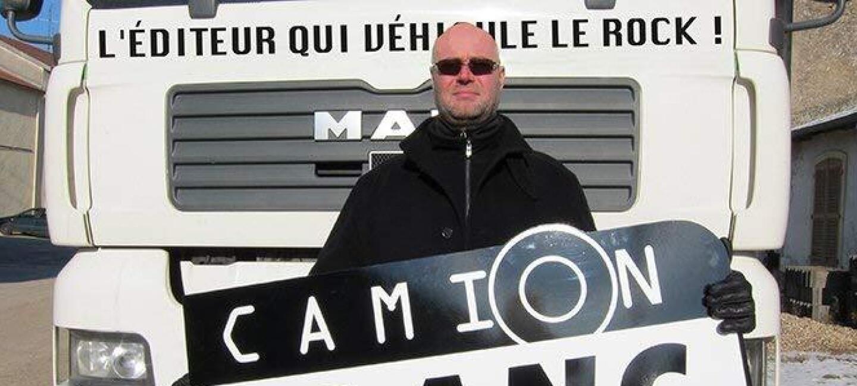Un homme portant des lunettes de soleil se tient devant un camion blanc en tenant dans ses mains la pancarte de la maison d'édition Camion Blanc