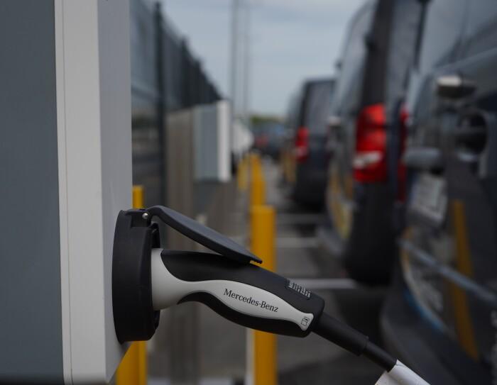 Una Mercedes Benz-Vans en un aparcamiento. Se ve el logo Prime de Amazon y el texto en la puerta 100% Eléctrico Envíos 'Shipment Zero'. En primer plano se ve un cargados de batería que está subministrando electricidad a la furgoneta de al lado que solo se ve un poco su parte trasera.