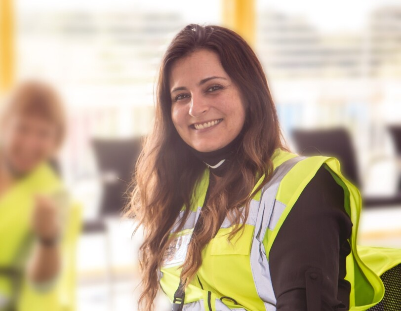 Eine lächelnde junge Frau mit langen braunen Haaren und Sicherheitsweste.