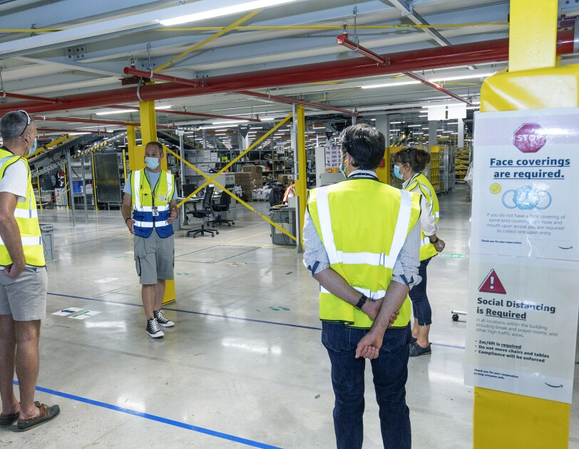 British Chambers of Commerce members on a tour of the Amazon fulfilment centre in Bristol, they are social distancing and wearing protective face masks and yellow hi-vis jackets in a fulfilment centre.