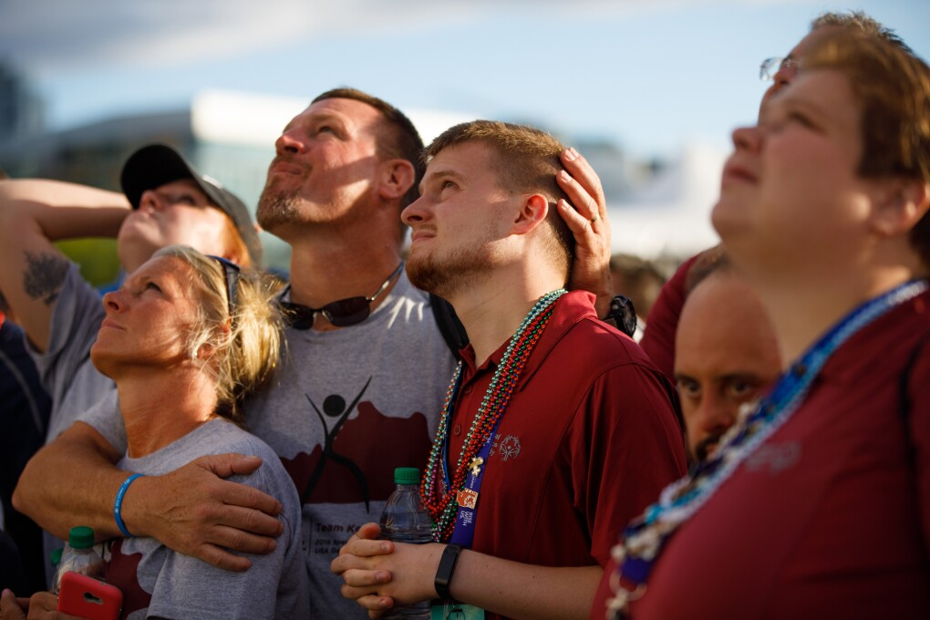 Special Olympics attendees are watching the closing ceremony festivities. In the photo, attendees are looking upward. A man embraces a woman and a younger man, as they all look skyward.