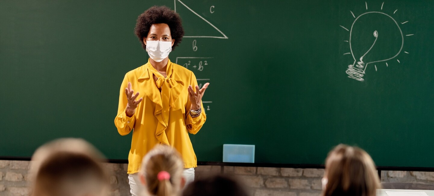 A teacher stands in front of a classroom wearing a face mask and speaking to children seated in the room with masks on. There is a chalkboard behind the teacher with a math equation written down in the center of the board and a light bulb drawn in the corner.