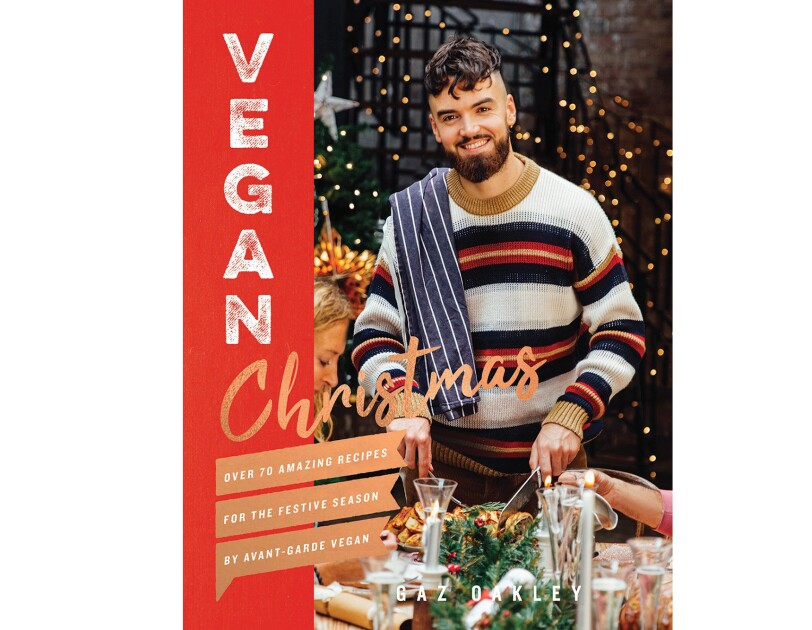 Vegan Christmas cookbook features a man wearing a sweater, with a dish towel thrown over his shoulder, carving into a dish. On either side of him are guests at his table, appearing to enjoy a holiday meal.