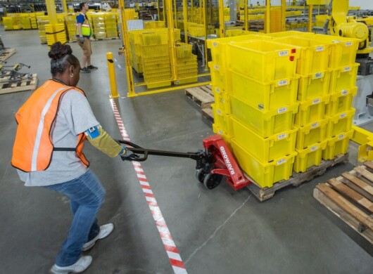 A female Amazon employee pulls a pallet of packing cartons with a hand truck in an Amazon Fulfillment center
